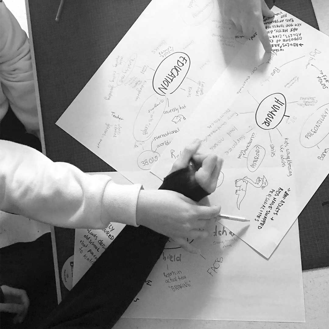shows collaborative design process, three hands stretch over piece of paper showing sketches and mind mapping. brainstorming, creative, dinosaurs, graphic design, branding.
